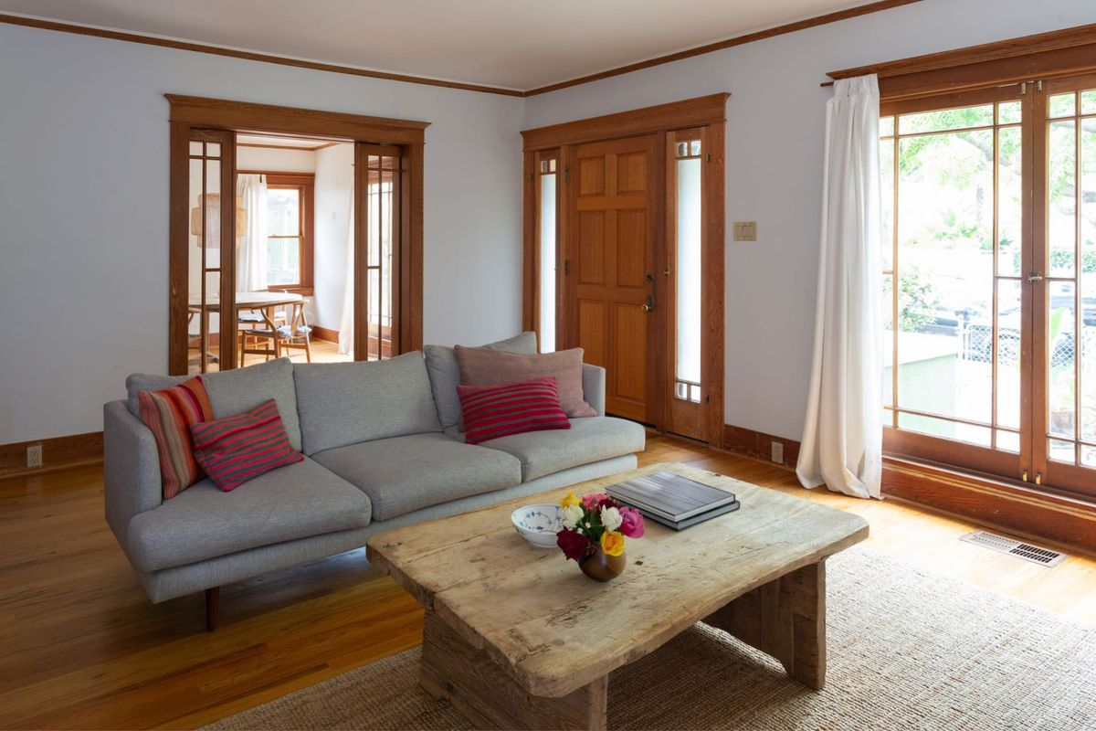 A living room with a sofa, a large coffee table, and hardwood floors.