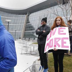 """Alisa Evans hold a two-sided sign reading """"Love more, fear less"""" at the protest held by Utah Against Police Brutality outside the Salt Lake City Public Safety Building in Salt Lake City Saturday, Jan. 10, 2015."""