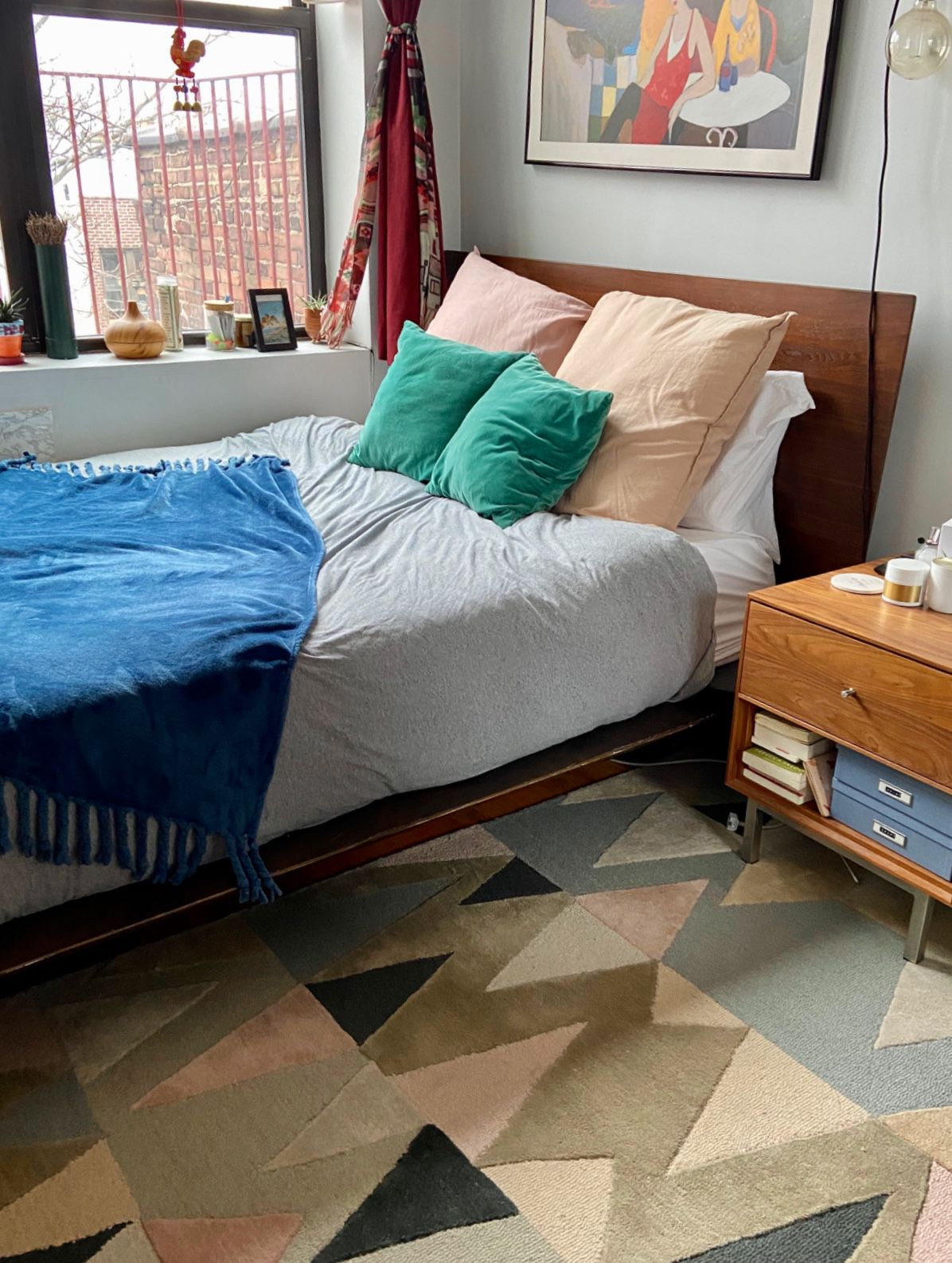 A rug with zig-zag pattern sits next to a wooden platform bed.