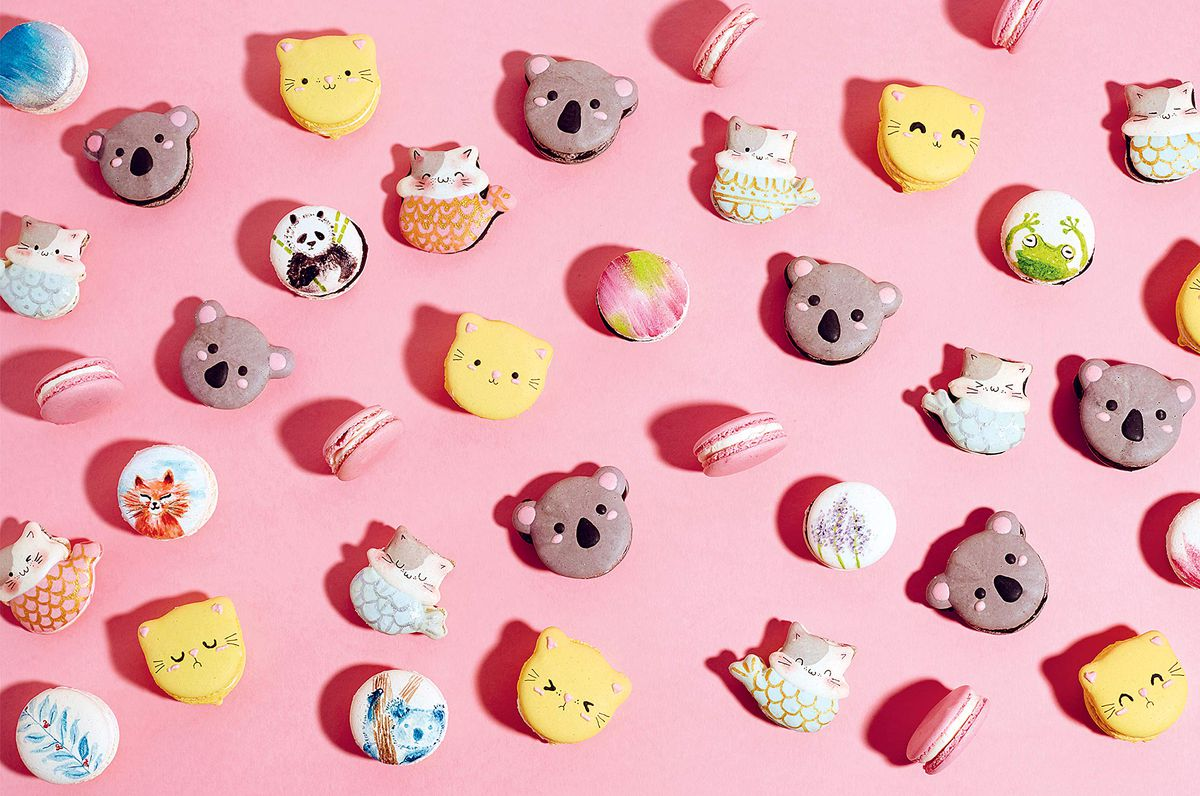 Cookies decorated as animals that look like cartoon characters on vibrant pink background.
