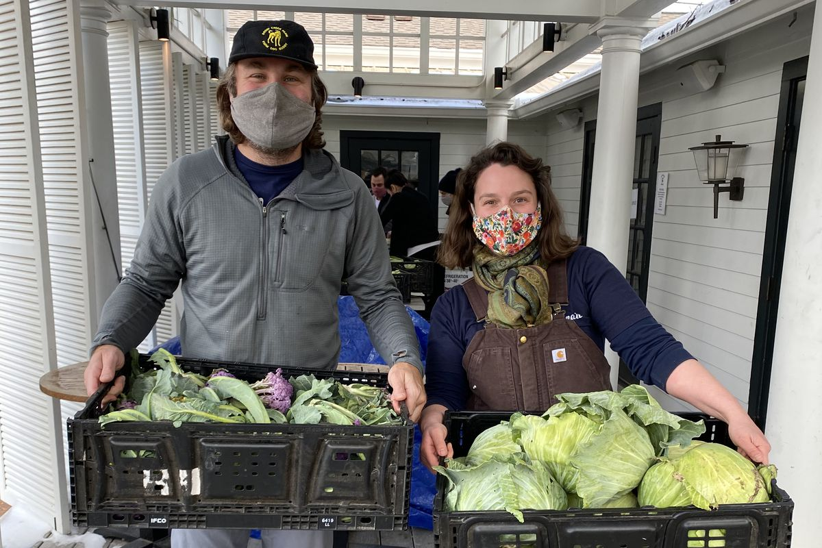 Olamaie chef Michael Fojtasek and Hat & Heart Farm co-owner Katherine Tanner holding crates of green vegetables