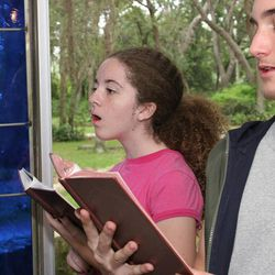 A teen boy and girl sing hymns in church.