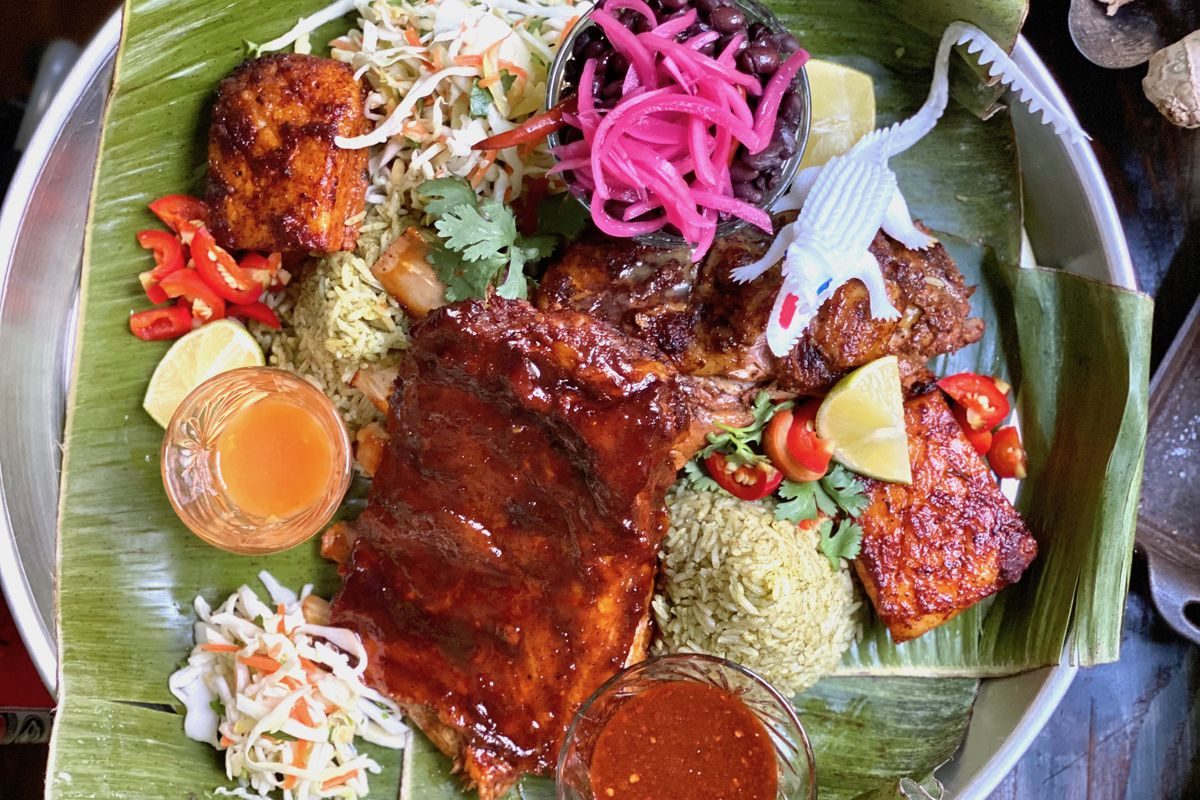 round tray with banana leaves covered in colorful dishes including meat, vegetables, and sauces
