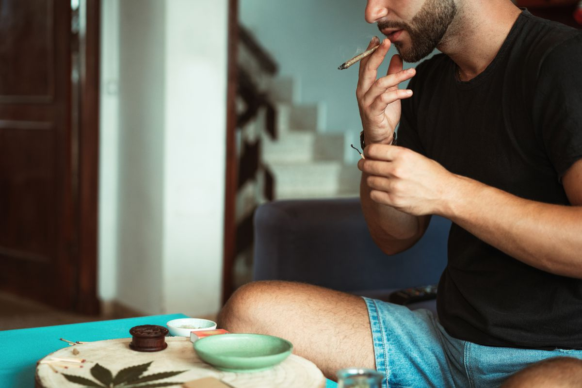 A man smoking a joint on a couch