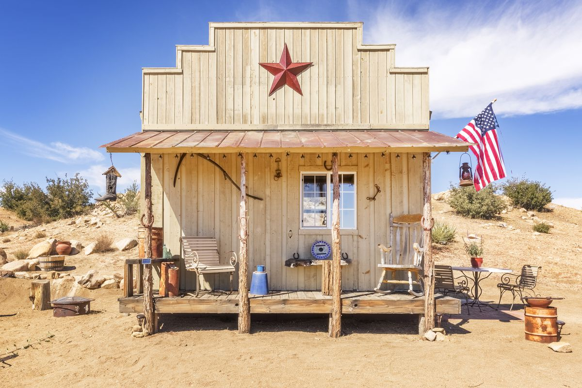 Tiny wood-framed home with covered front porch and stepped roof line and star decoration sitting on a desert site.