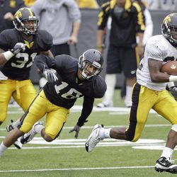 Iowa running back Damon Bullock, right, runs from defenders Micah Hyde (18) and Anthony Hitchens, left, during a touchdown run in Iowa's annual NCAA college football spring scrimmage, Saturday, April 14, 2012, in Iowa City, Iowa.