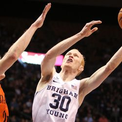 Brigham Young Cougars guard TJ Haws (30) hooks the ball over the arm of Idaho State Bengals guard Jared Stutzman (21) as BYU takes on Idaho State at the Marriott Center in Provo on Thursday, Dec. 21, 2017.