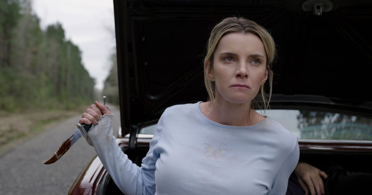 A determined-looking blonde woman in a simple light-blue blouse clutches a bloody hunting knife and stands with her back to an open car trunk with a body barely visible inside the trunk.