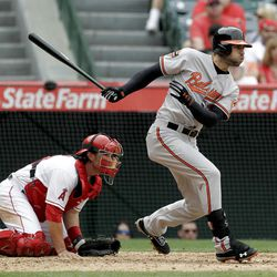 Baltimore Orioles' Nick Markakis drives in the winning run as Los Angeles Angels catcher Bobby Wilson looks on during the 10th inning of a baseball game in Anaheim, Calif., Sunday, April 22, 2012. (AP Photo/Chris Carlson)