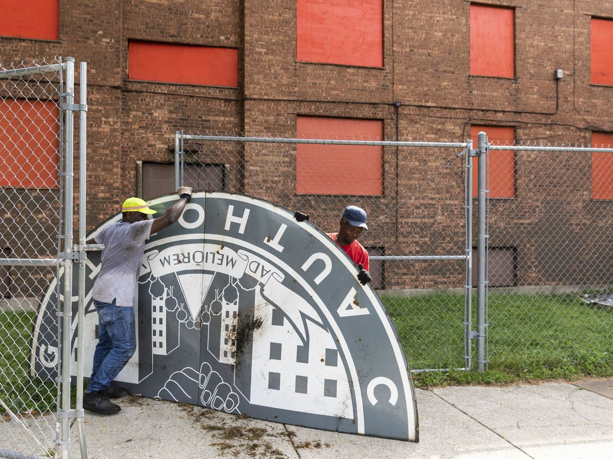 Thomas Taylor (grey shirt), 54, of North Lawndale, and 59-year-old Wayne Flax, of Austin, both workers with McKay Landscaping, work to dismantle and take into storage an old Chicago Housing Authority sign sitting outside the sole remaining building from t