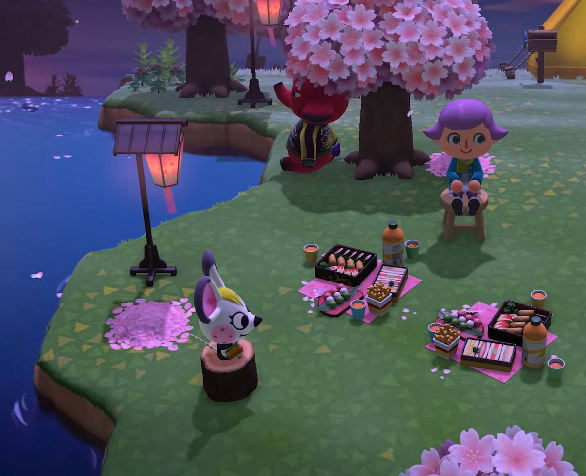 Animals sit around a villager at night under cherry blossom trees in Animal Crossing: New Horizons on Nintendo Switch