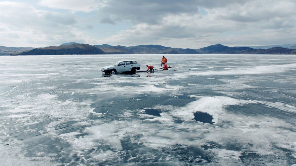 four people in orange jackets standing on ice and replacing a white car's tire in Aquarela