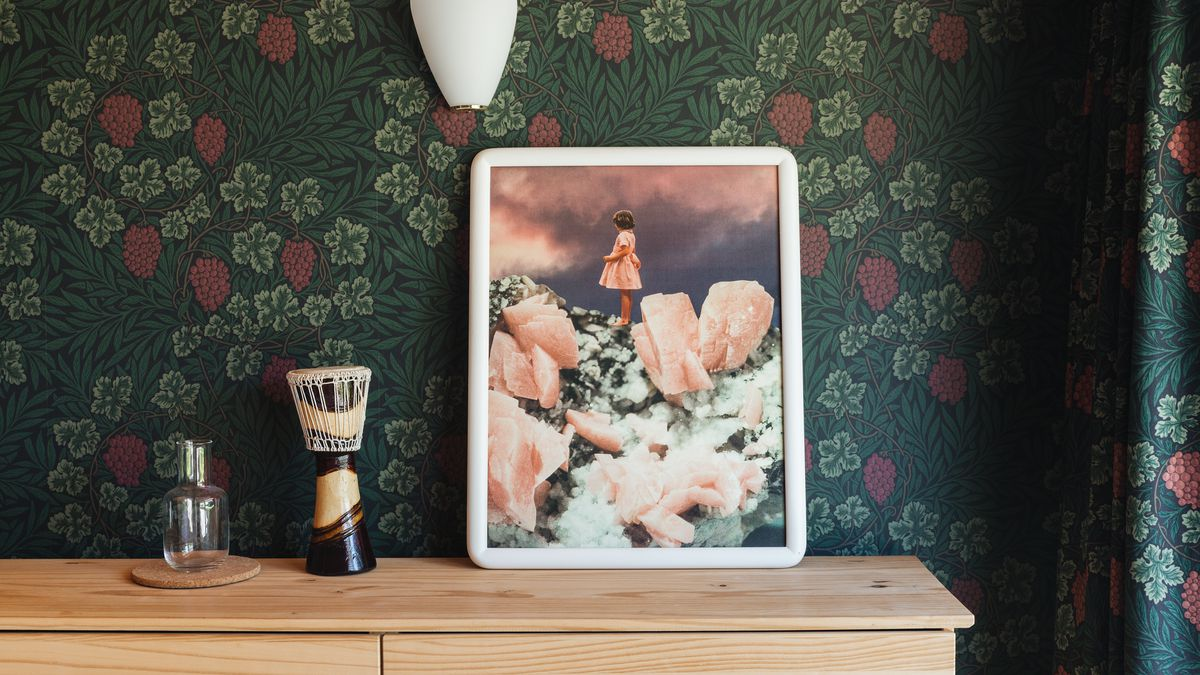 Dark green wallpaper covers a bedroom, which is decorated with a dresser, art, and a wall sconce.