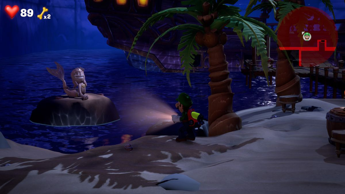 Luigi stares at a statue of a ghost mermaid on a beach in Luigi's Mansion 3