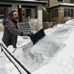 Sarah Lee clears snow off her vehicle in Edgewater as a winter snow storm batters Chicago, Tuesday morning, Jan. 26, 2021.