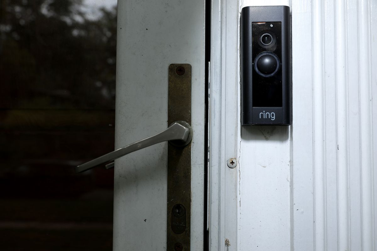 Image of an Amazon Ring doorbell camera mounted beside the handle of a house's front door.