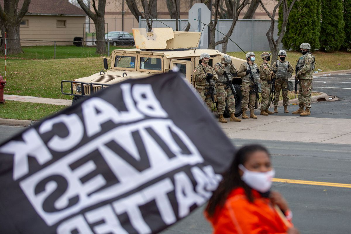 A Black woman in a vibrant orange rain coat parades a giant Black Lives Matter flag in front of a flank of National Guardsmen standing in front of a sand-colored humvee in the Minneapolis suburb of Brooklyn Center