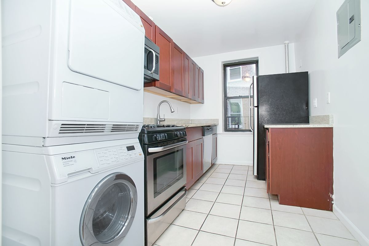 A kitchen with white walls, a small window, wood cabinetry, and in-unit washer/dryer.