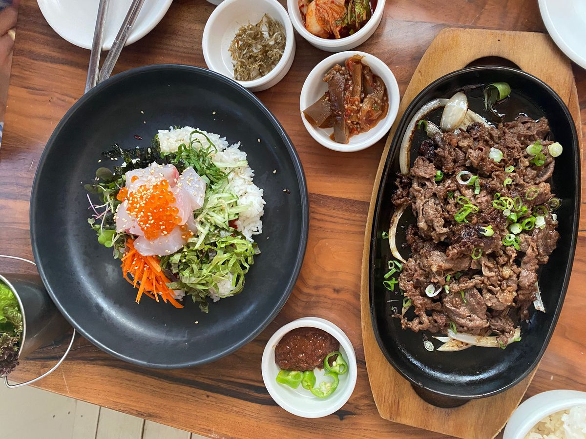 An overhead photograph of two dishes. One consists of rice, mixed greens, shredded carrots, and an egg; the other appears to be made from grilled meat