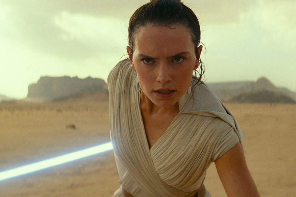 Daisy Ridley as Rey, holding a lightsaber in the desert