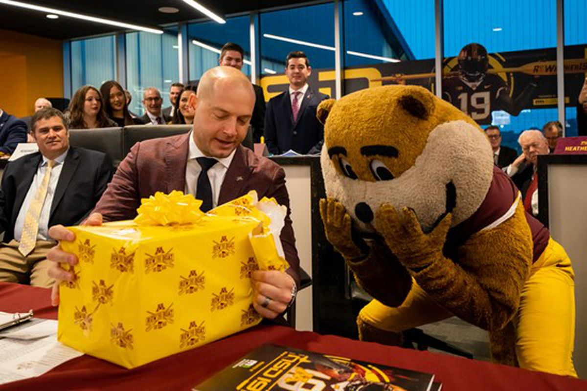 P.J. Fleck opening a gift from Goldy