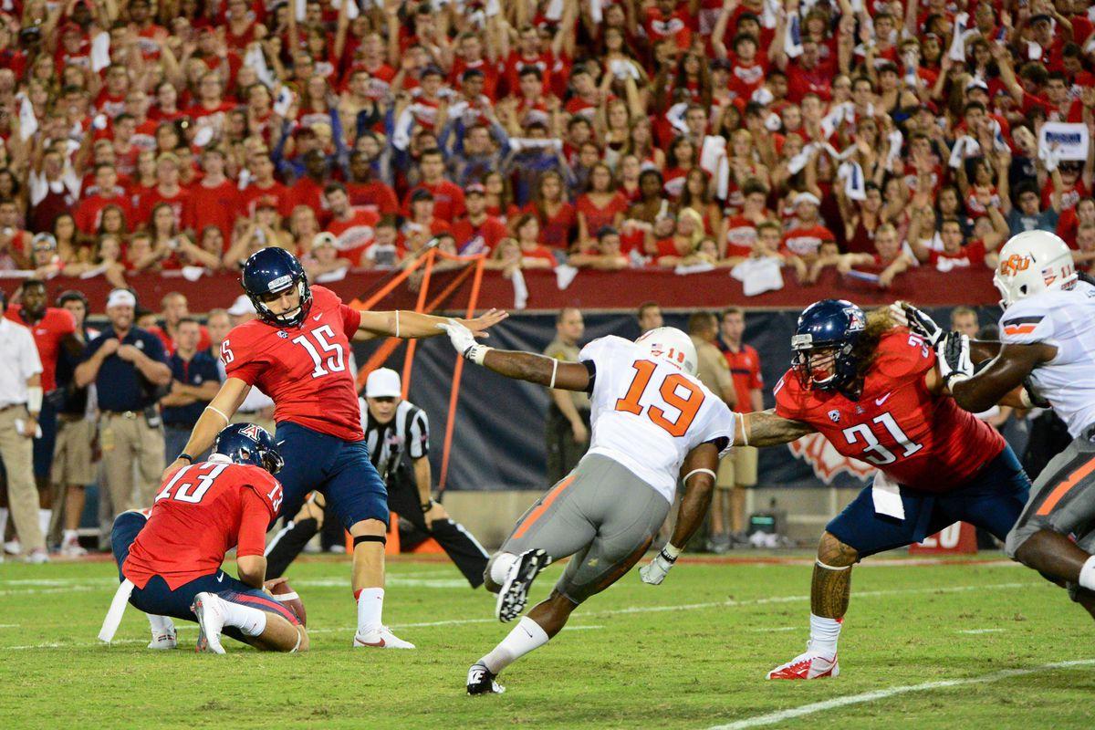 Sept. 8, 2012; Tucson, AZ, USA; Arizona Wildcats kicker John Bonano (15) kicks a 25 yard field goal while under pressure from Oklahoma State Cowboys cornerback Brodrick Brown (19) during the first half at Arizona Stadium.