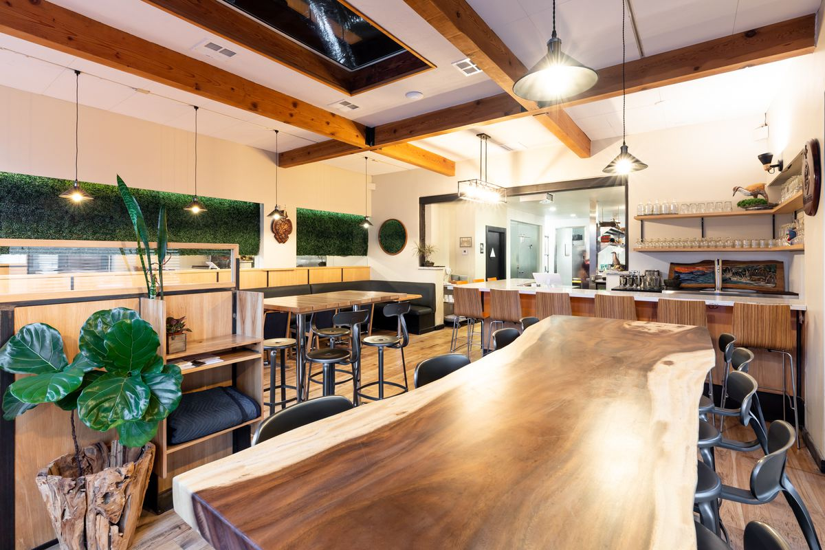 A long communal table, made with live-edge wood, in the bar area