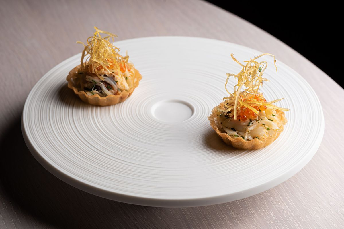Two crab tarts on a fine dining circular white plate.