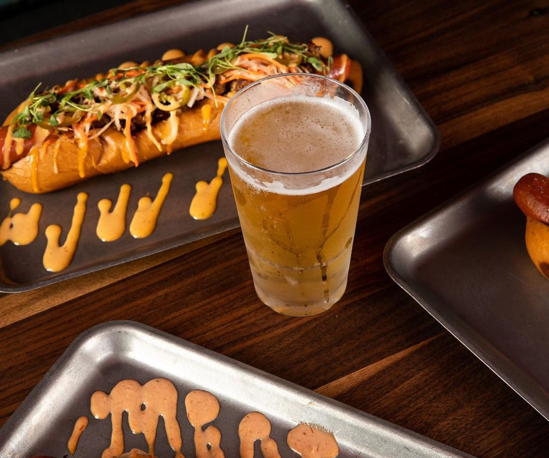 Two hot dogs with a glass of beer in the middle