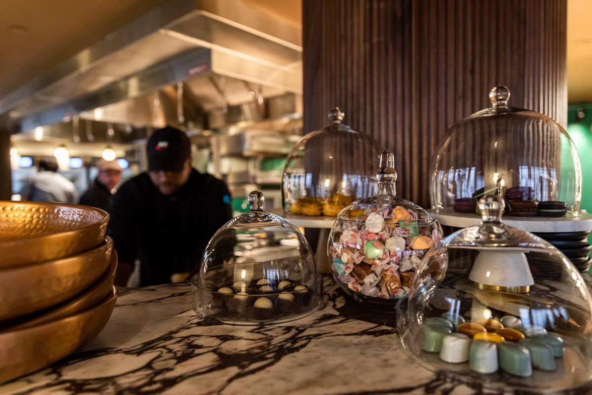 Candies, bonbons, and macarons sit under glass next to the kitchen at the Highlands.