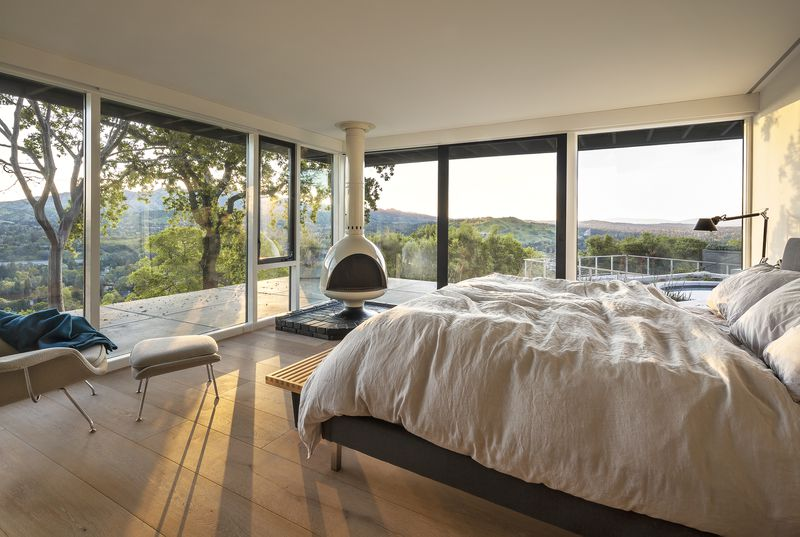 A bedroom with glass walls and a terrace overlooking mountains.