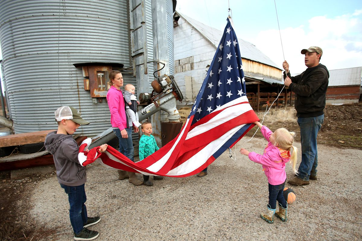 Addison Hicken, with the help of two of his kids Evan and Laynie, begin to put up their American flag on their farm in Heber on Wednesday, March 11, 2020. Jenn Hicken watches with their youngest son, Ren, and two nephews, Parker and Weston Walton.