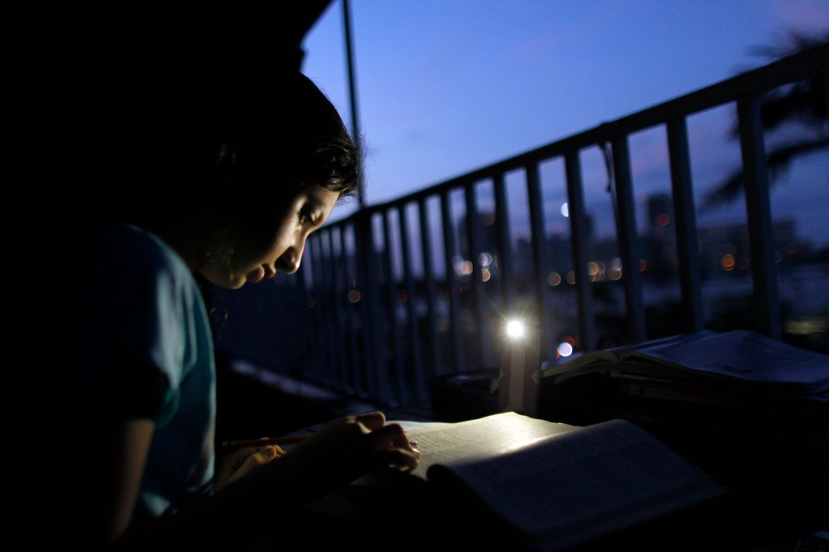 Alana Rivera Age 10 Does Her Homework On Apartment Balcony Lit By A Cell Phone In San Juan Puerto Rico November 2017