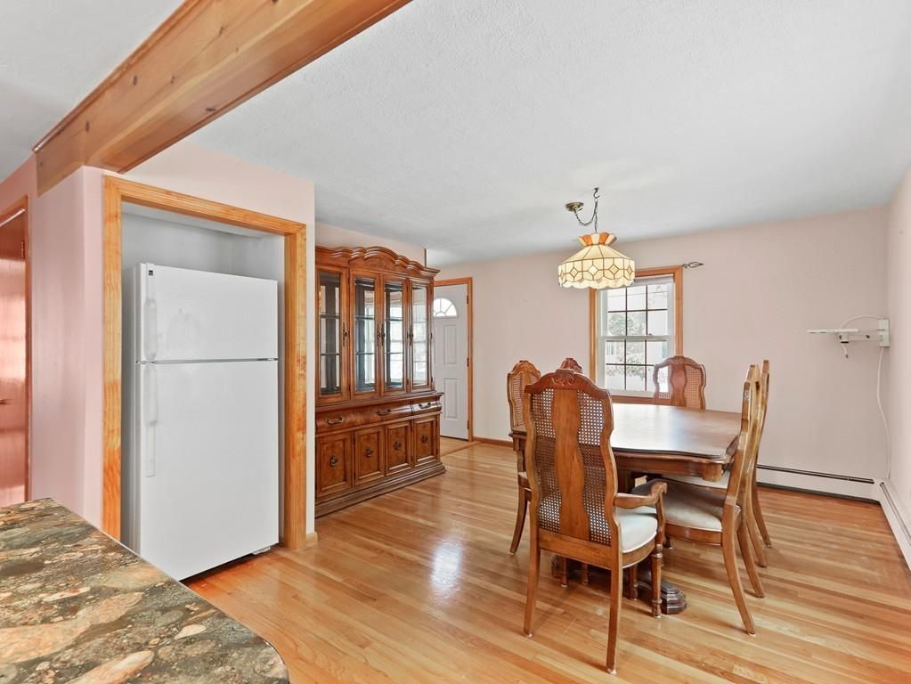 A dining room with a table and chairs and a credenza, and there's a large fridge in an alcove.