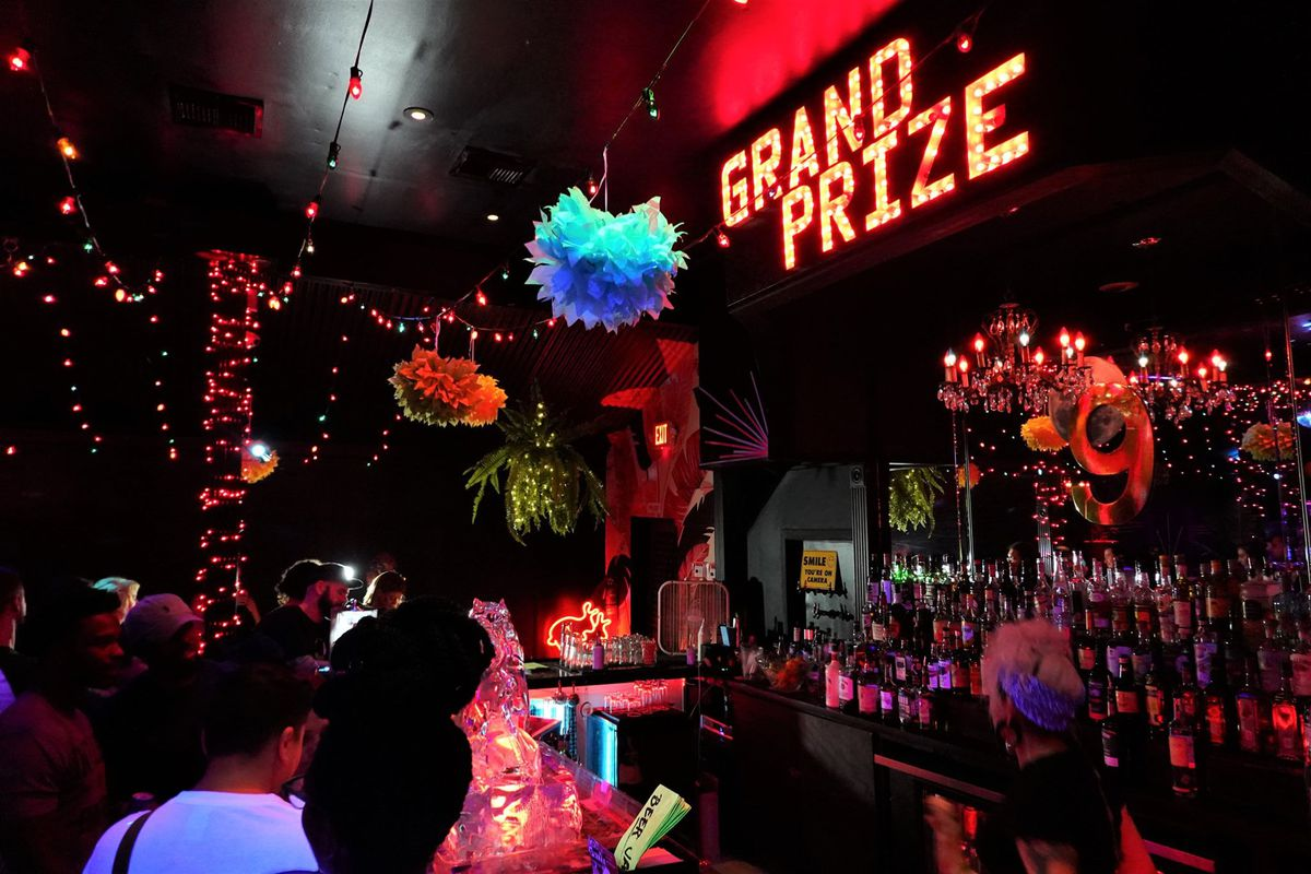 """a brightly-lit bar with a big neon sign on the right that reads """"grand prize"""""""