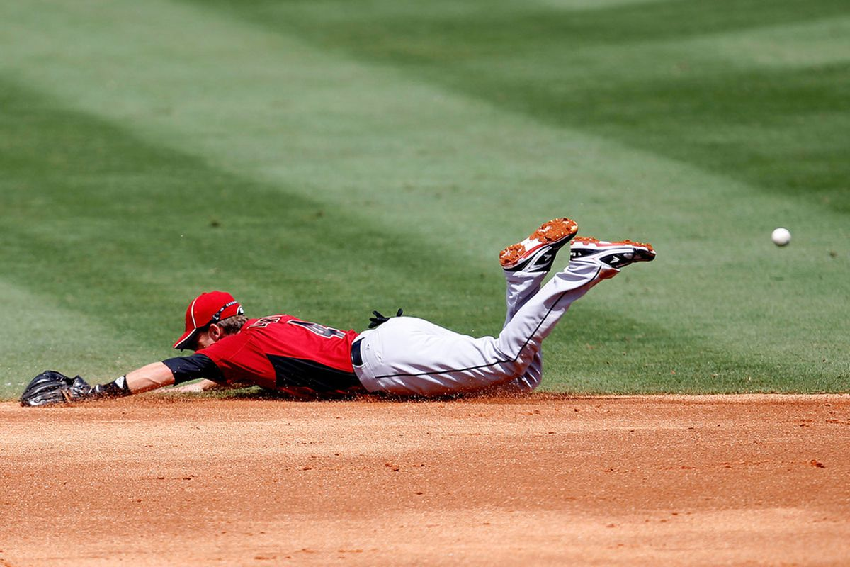 JUPITER, FL - MARCH 14:  Jed Lowrie #4 of the Houston Astros dives for a ball during a game against the St. Louis Cardinals at Roger Dean Stadium on March 14, 2012 in Jupiter, Florida.  (Photo by Sarah Glenn/Getty Images)