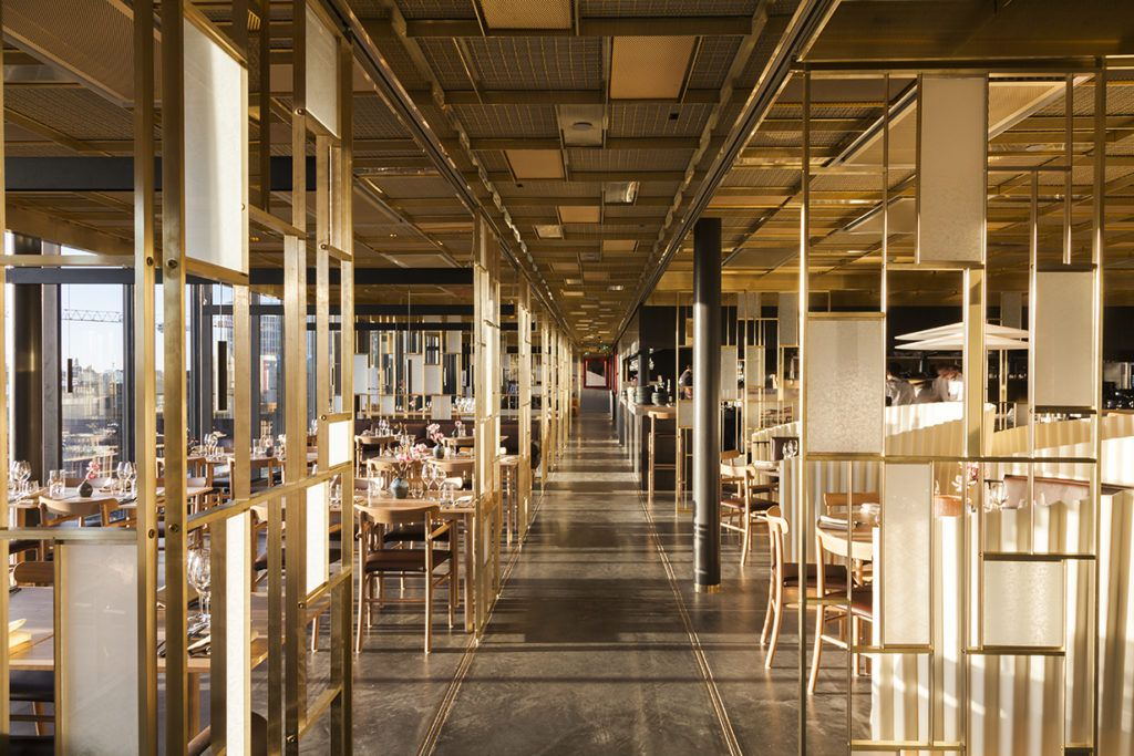 A long, light-filled dining room with geometric wooden room dividers