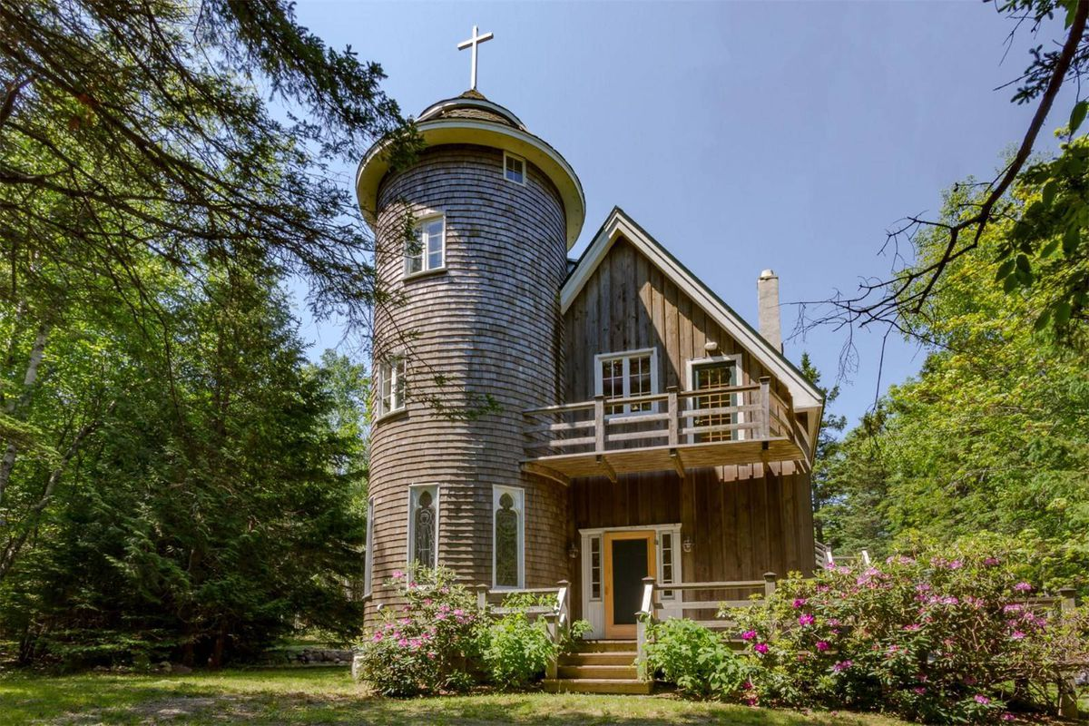 Wood-framed house with circular tower set on greenery.