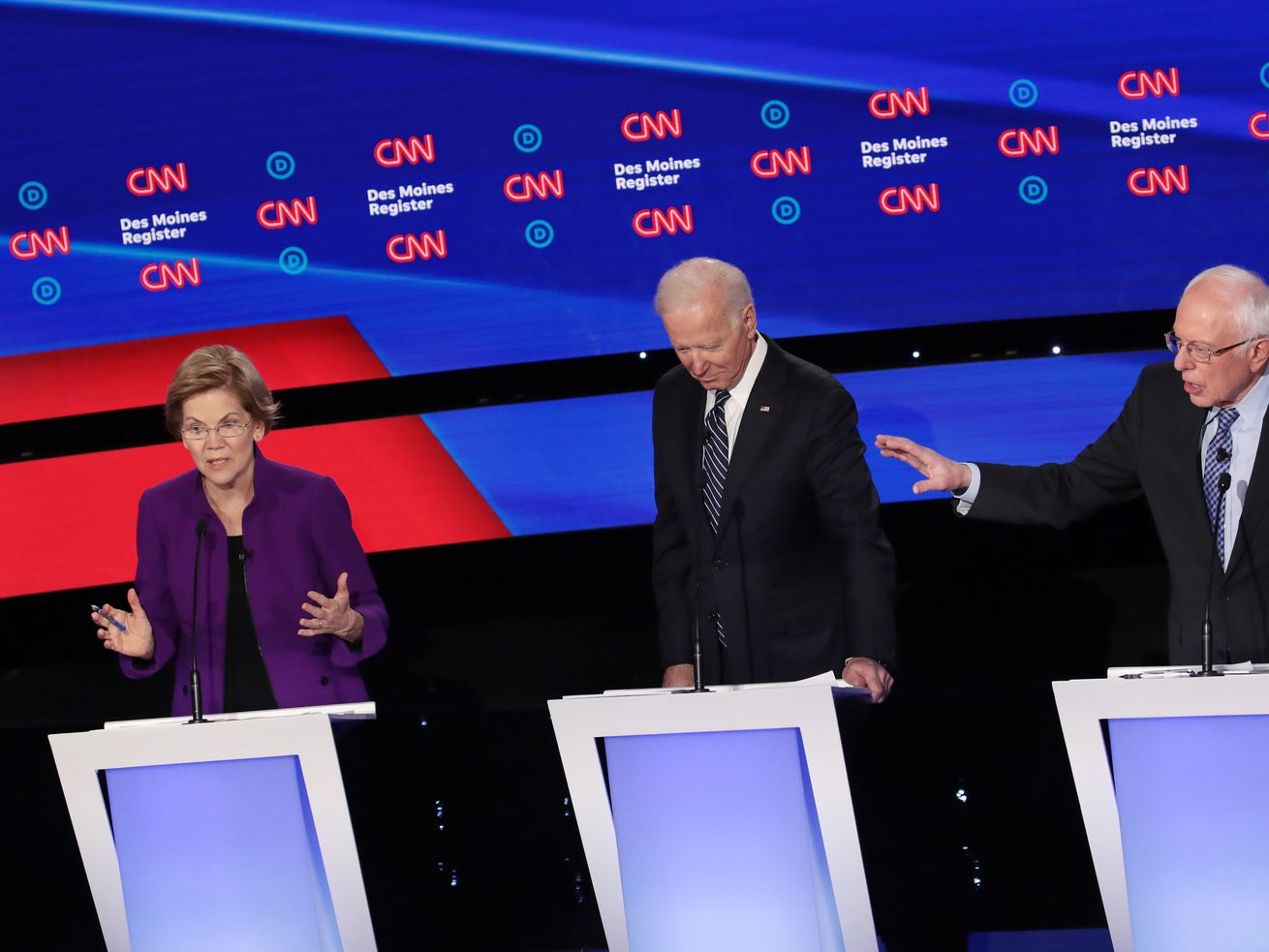 Senator Elizabeth Warren and Senator Bernie Sanders speak on the debate stage as Joe Biden  listens.