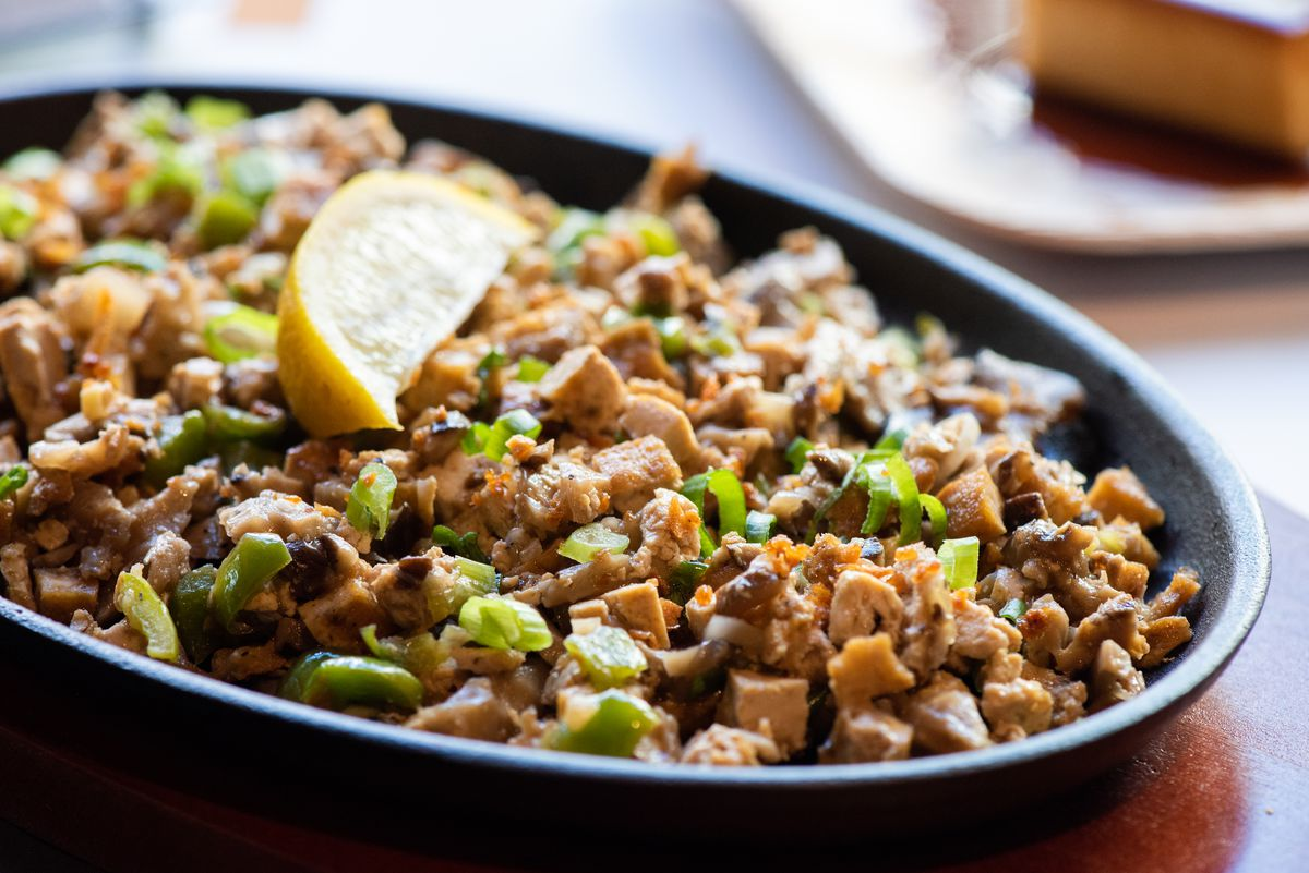 Mushroom and tofu sisig on a sizzling plate, topped with a wedge of lemon