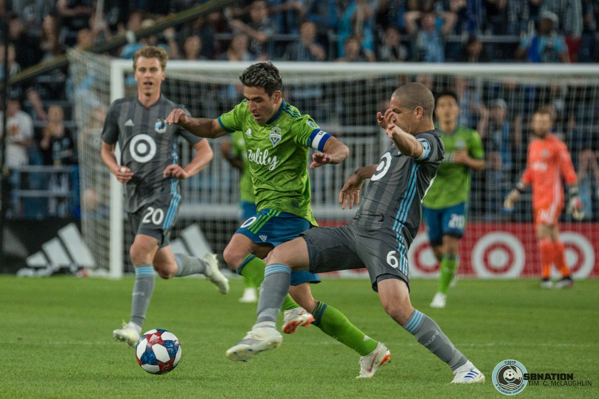 Ozzie Alonso and Nicolas Lodeiro fight for a ball during a 1-1 draw between Minnesota United and the Seattle Sounders