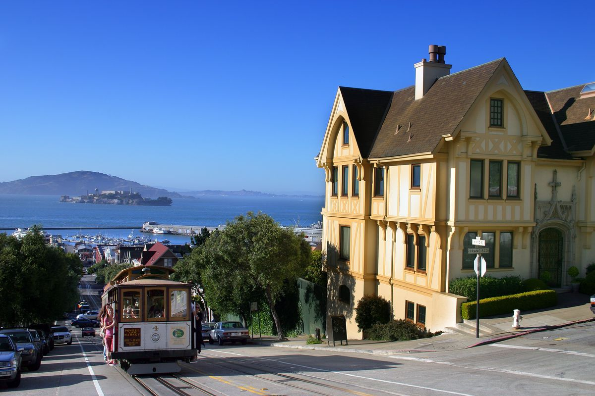 A cable car passing by a yellow stick Victorian house.