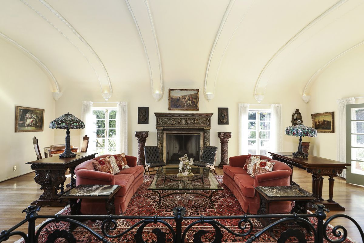 A room with coved ceilings and a tall ornamental fireplace