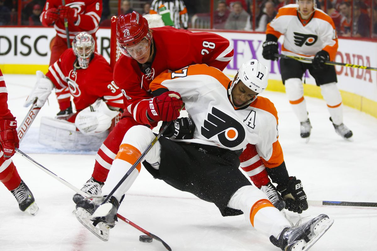Alex Semin plays defense in front of Cam Ward against the Flyers
