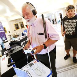 Karl Smith, who is visually impaired, tries out the Verity voting system from Heart Intercivic at the state Capitol in Salt Lake City on Wednesday, Aug. 2, 2017. Members of the public will be able to try out five different machines the state is considering buying.