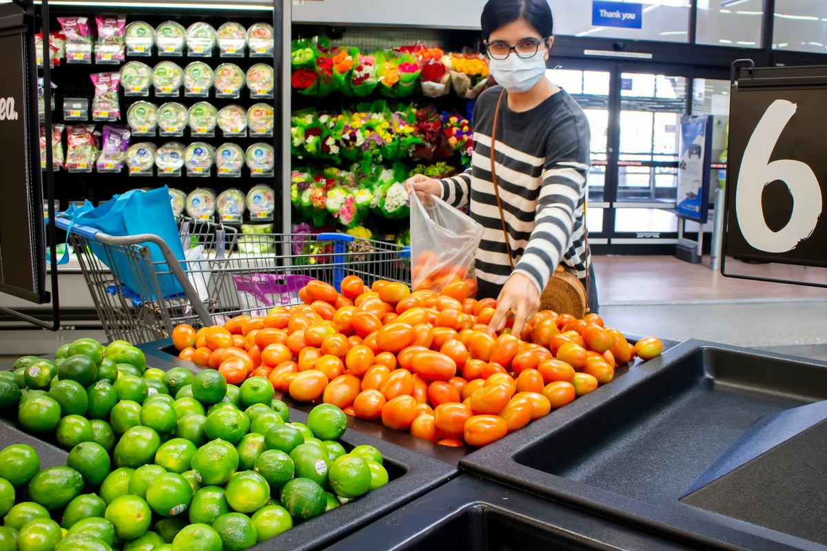 A woman shops for produce at a grocery store while wearing a face mask