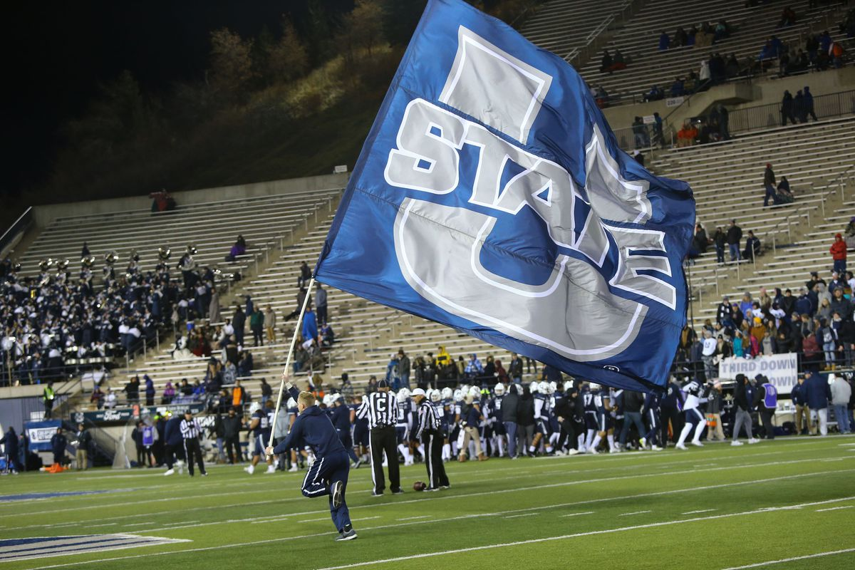Utah State cheer squad member runs down the field with a school flag during the second half against Boise State.