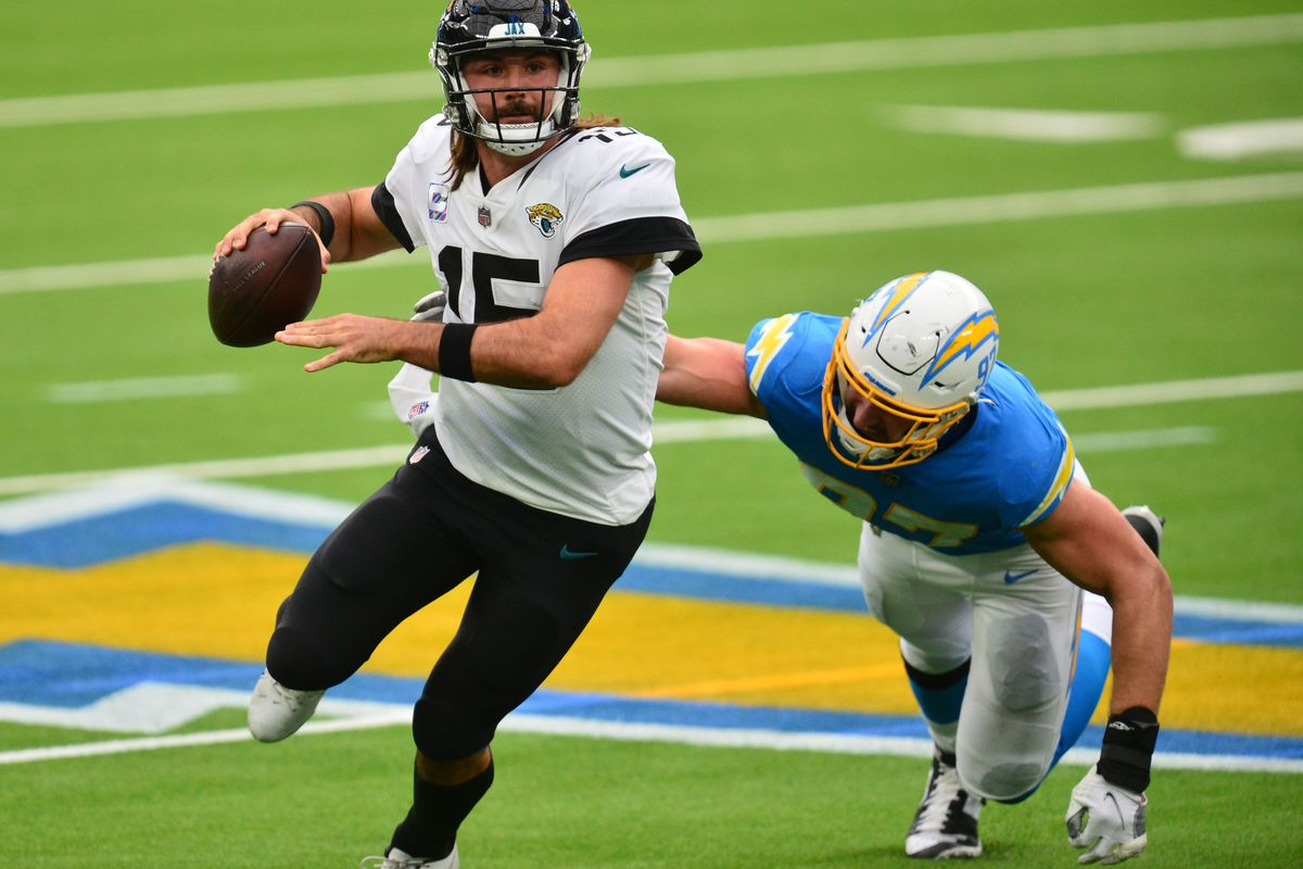 Jacksonville Jaguars quarterback Gardner Minshew runs the ball as Los Angeles Chargers defensive end Joey Bosa moves in during the first half at SoFi Stadium.