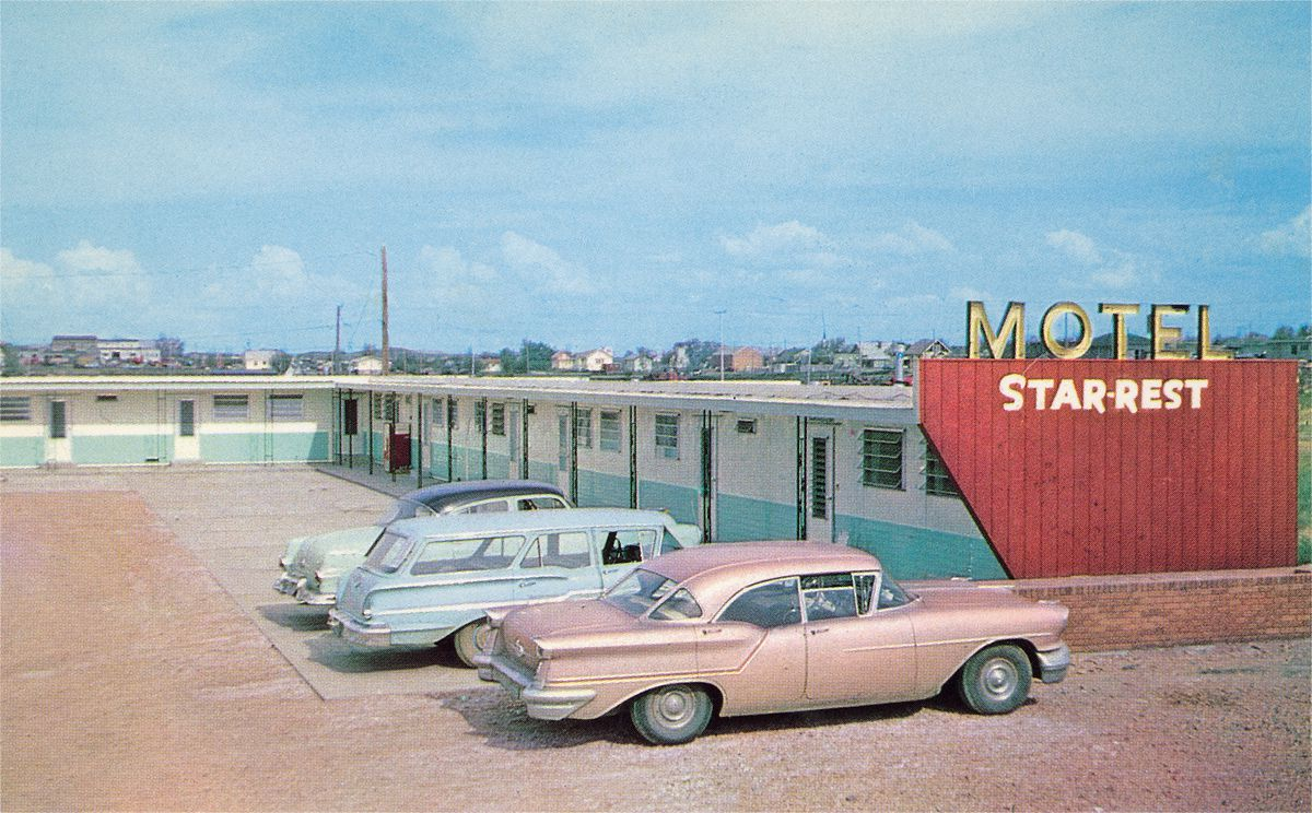 Vintage color photograph in dreamy blue and pink tones featuring the Motel Star-Rest, a single-story pale blue-and-white metal structure with jalousie windows and doors and a parking lot with three 1950s cars.