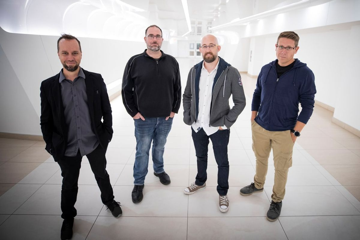 Four game developers in a publicity shot, all looking at the camera with hands in pants pockets.